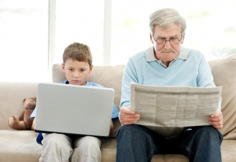 old man newspaper young boy lap top